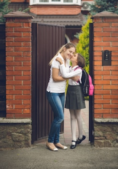 Школьница в униформе целует мать перед школой