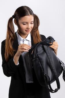 Школьница в форме открывает свой портрет черной сумки на белом изолированном фоне