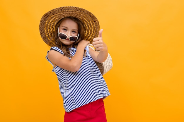 Schoolgirl is going on a trip, photo of a girl in a beach hat on a yellow background