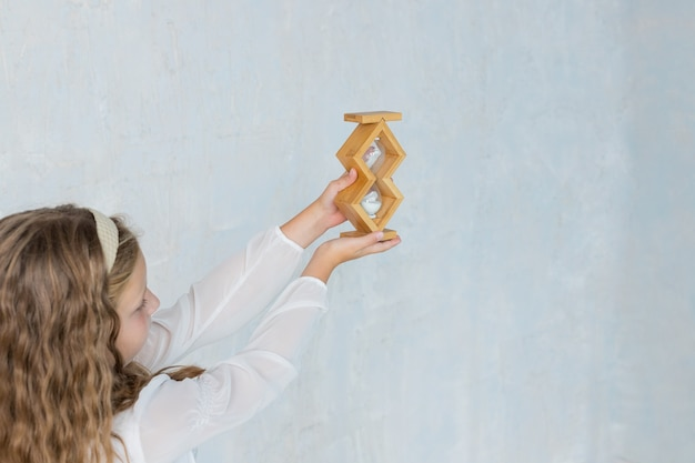 Schoolgirl is holding sandglass in classroom small girl in time management concept education and sch...