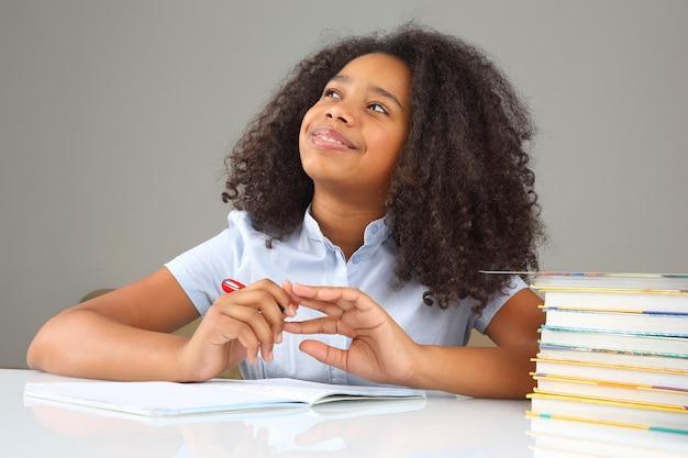Школьница думает о школьной домашней работе, делает домашнее задание