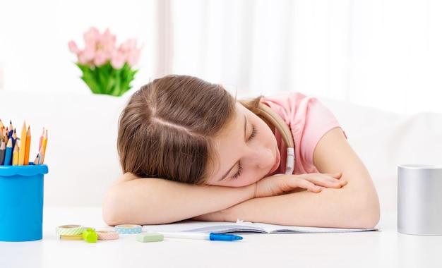 女子高生は疲れていて、屋内の机で寝ています