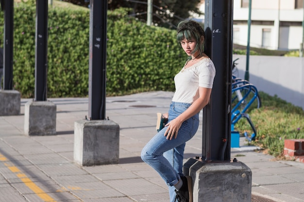 Schoolgirl leaning on pillar