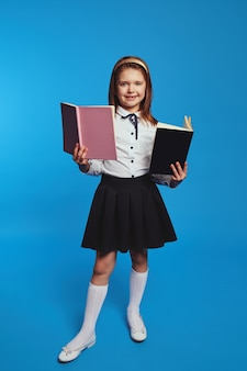Школьница изучает информацию из учебников позы на синем фоне