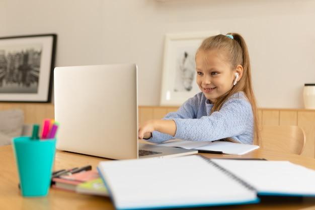 Школьница смотрит на экран ноутбука и улыбается.