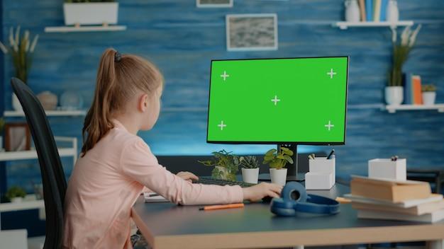 Schoolgirl looking at computer with horizontal green screen