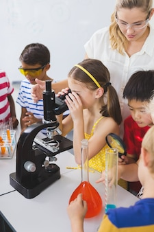 Schoolgirl looking through microscope in laboratory
