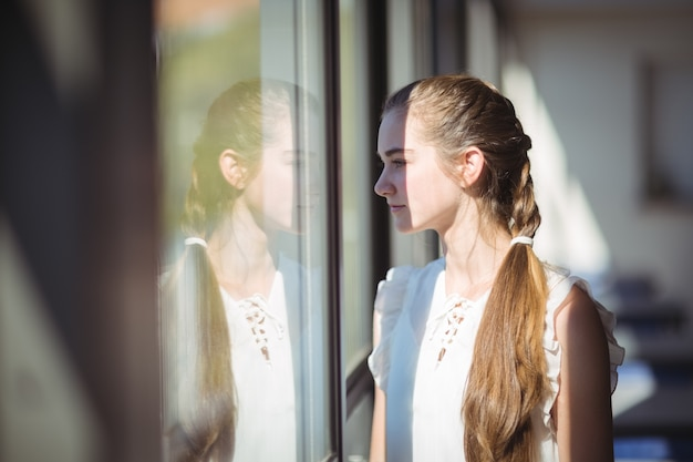 Schoolgirl looking through window in classroom