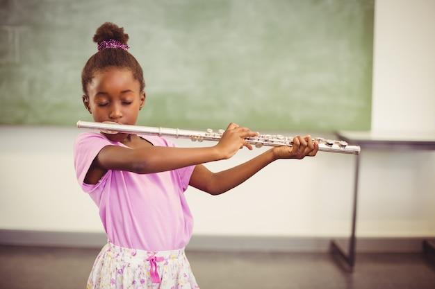 Schoolgirl playing flute in classroom