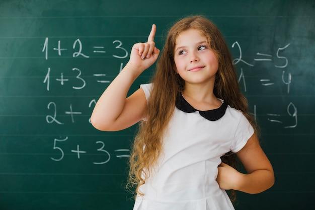 Schoolgirl pointing up in class