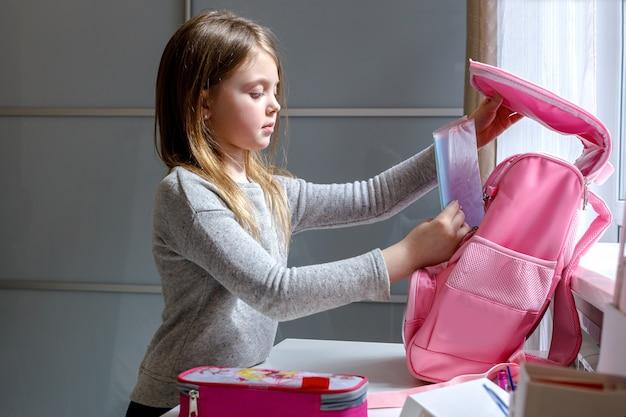 Школьница готовится к школе, собирая книги в школьной сумке