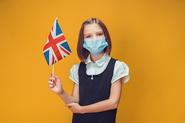Schoolgirl in protective medical mask with great britain flag on yellow background safety concept