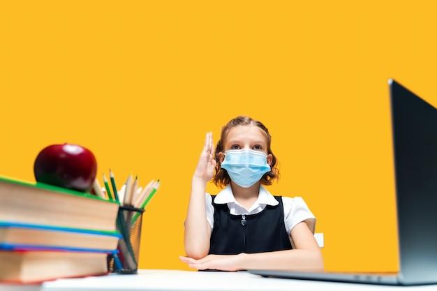 여학생이 손을 들고 마스크를 쓰고 노트북에 앉아 노란색 배경 원격 학습