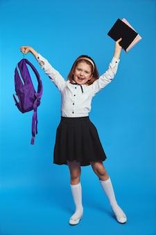 Школьница поднимает кучу книг и рюкзак в руке и улыбается
