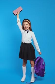 Школьница поднимает кучу книг, держа в руке рюкзак и улыбается