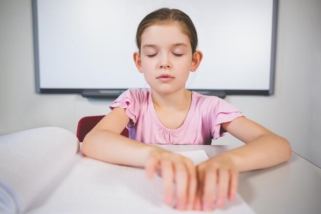 教室で点字の本を読んでいる女子高生