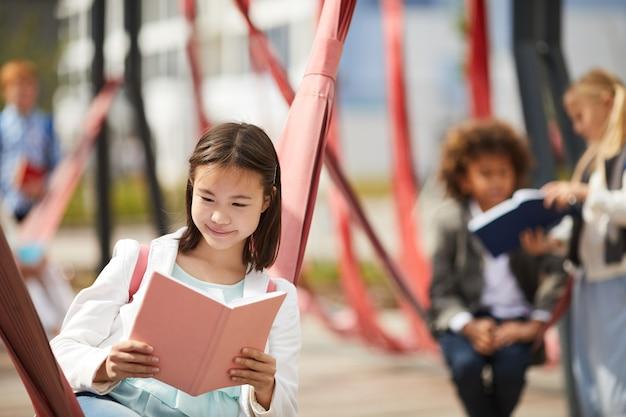 Schoolgirl reading a book outdoors