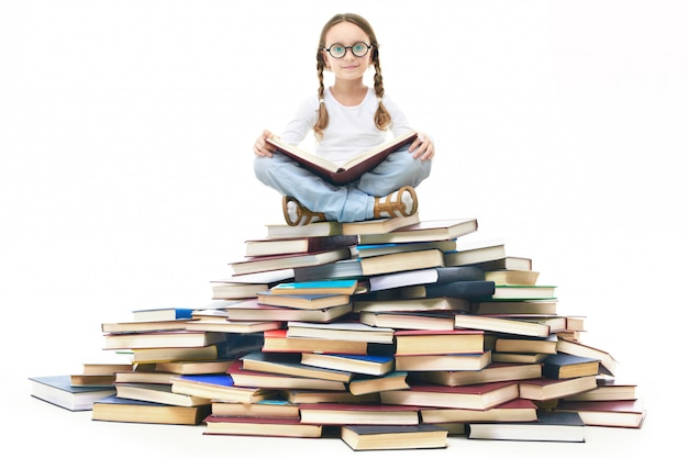 Schoolgirl reading on a pile of books