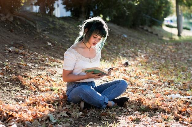 Schoolgirl reading on sunny hill