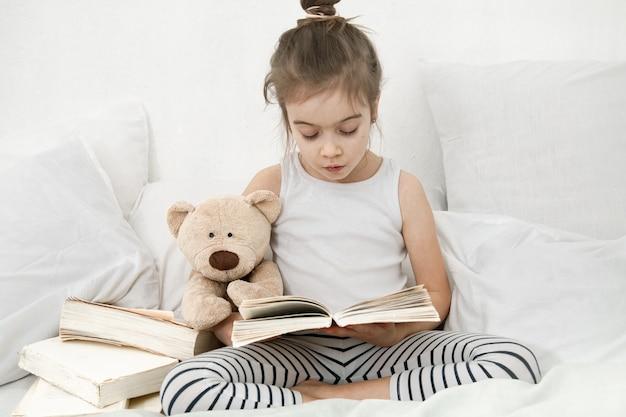 女子高生はテディベアと一緒にベッドでパジャマを着て本を読みます。子どもの発達と自己啓発の概念。