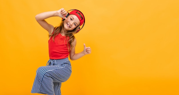 Schoolgirl in a red t-shirt and jeans dancing energetically on a yellow background, emotional portrait