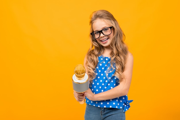 Schoolgirl reporter with a microphone in her hands on a  of an orange wall, smiling and looking at the camera