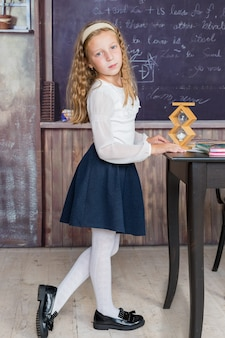 Schoolgirl and sandglass in classroom small girl in time management concept education and school con...