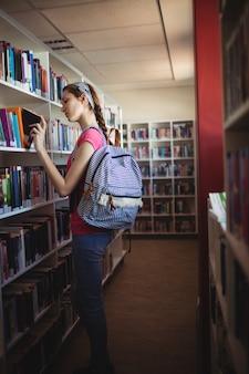 図書館で本を選択する女子高生