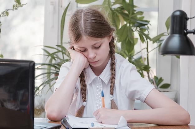 숙제를 위해 노트북을 사용하는 여학생의 자가 격리. 게임, 교육, 학교 개념 - 노트북과 집에 있는 슬픈 소녀. 온라인으로 숙제를 하는 데 어려움을 겪고 있는 소녀, 우울한 실내에 앉아
