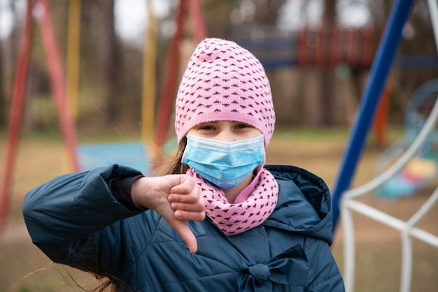 Schoolgirl showing thumbs down to show her irritation to constant wearing medical mask and ban on playing on playground. life during coronavirus epidemic