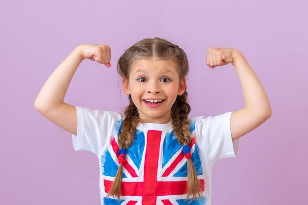 여학생은 밝은 자주색 배경에 그녀의 팔과 미소에 그녀의 근육을 보여줍니다.