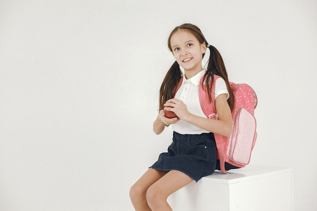 Schoolgirl sit on white cube. girl with backpack holding apple on white.