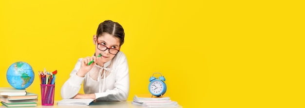 The schoolgirl sits at the desk and thinks about the decision of the task on yellow background. back to school. the new school year. child education concept. wide banner. copy space