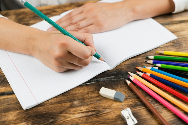 The schoolgirl sits at her desk and draws in a notebook with colored pencils.