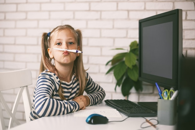 The schoolgirl sits at home at the table at the computer, plays with a pencil, plays with and laughs.