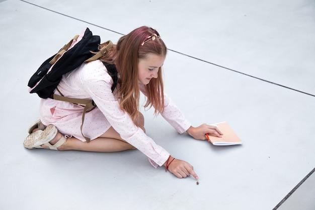 Школьница сидит на бетонных плитах школьного двора и рассматривает жука. экологичные подростки