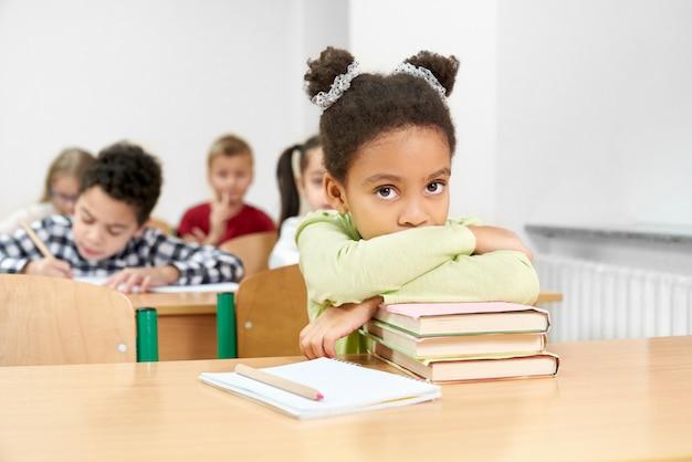 本にもたれて、教室の机に座っている女子高生。