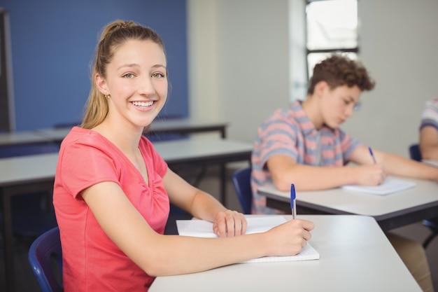 教室の机に座っている女子高生