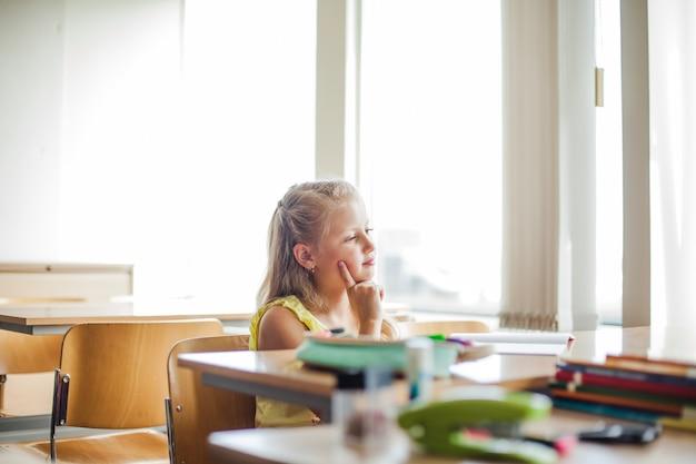 頬に触れる机に座っている女子学生