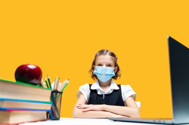 온라인 노란색 배경 원격 학습을 공부하는 마스크를 쓰고 노트북에 앉아있는 여학생