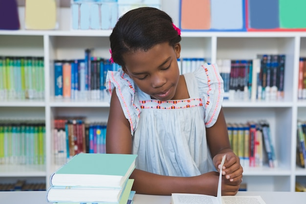 Школьница сидит на столе и читает книгу в библиотеке