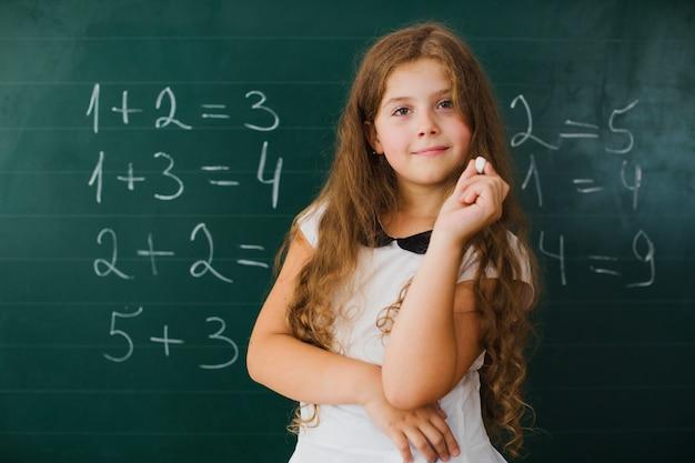 Schoolgirl smiling at blackboard in class