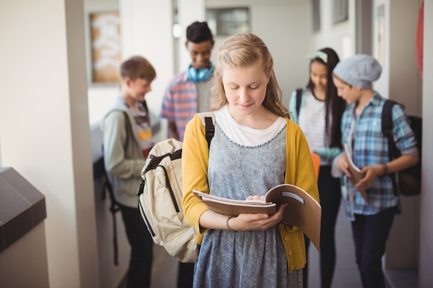 Школьница, стоя в коридоре, читая тетрадь