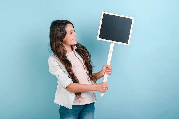 Schoolgirl stands holding an empty board in her hands and looking in it.
