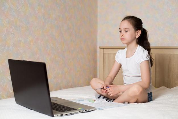 デジタルタブレットのラップトップのノートブックで自宅で勉強し、トレーニングの本が付いているベッドで学校の宿題をしている女子高生