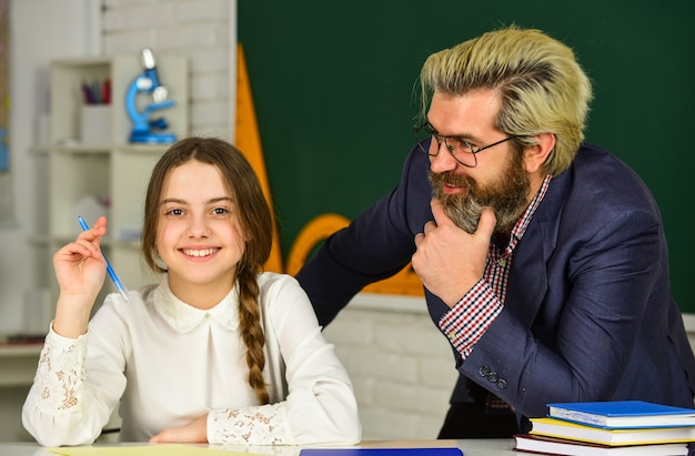 Schoolgirl studying. back to school. little girl and man against blackboard. knowledge day concept. child with teacher in classroom at school. happy teachers day. teacher and schoolgirl on lesson.