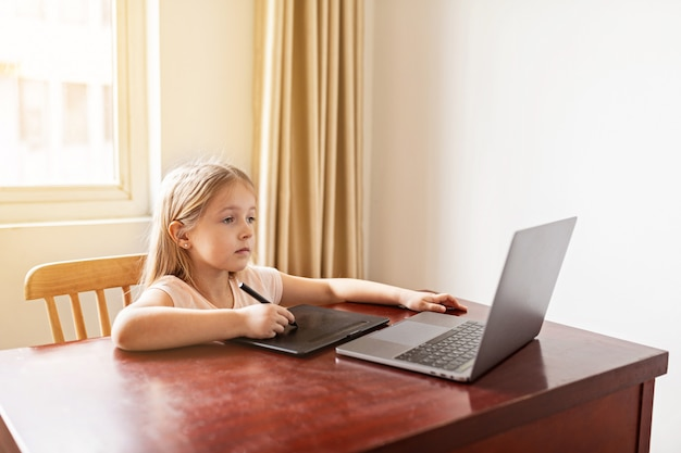 Schoolgirl studying homework during her online lesson at home