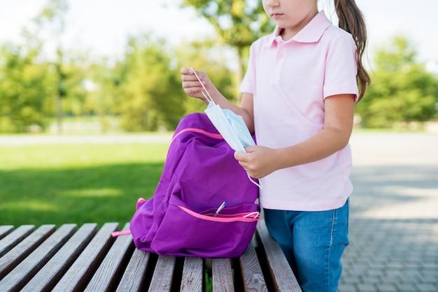 Школьница вынимает защитную маску из своего рюкзака