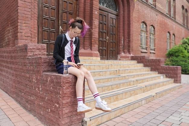 스마트폰을 사용하여 배낭과 제복을 입은 여학생 십대. 학교 건물 근처 소녀, 공간을 복사합니다. 다시 학교로, 다시 대학으로, 교육, 십대 개념