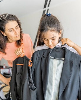 A schoolgirl tries on a new suit for school